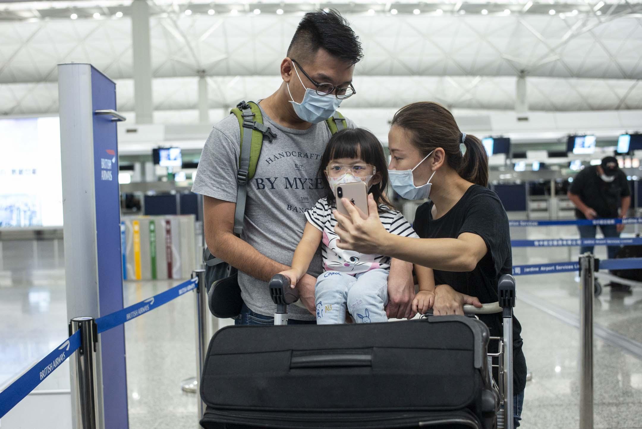 7月12日,Apple一家三口在香港國際機場,準備登機移民倫敦,在機場用視像通話跟親友道別。 攝:林振東/端傳媒