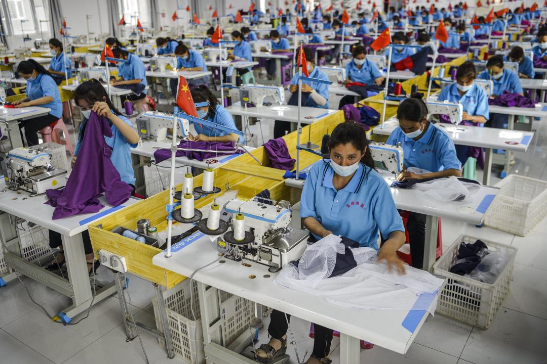 2020年6月18日中國新疆維吾爾自治區,工人戴着口罩在一家服裝廠工作。 攝:Liu Xin/China News Service via Getty Images