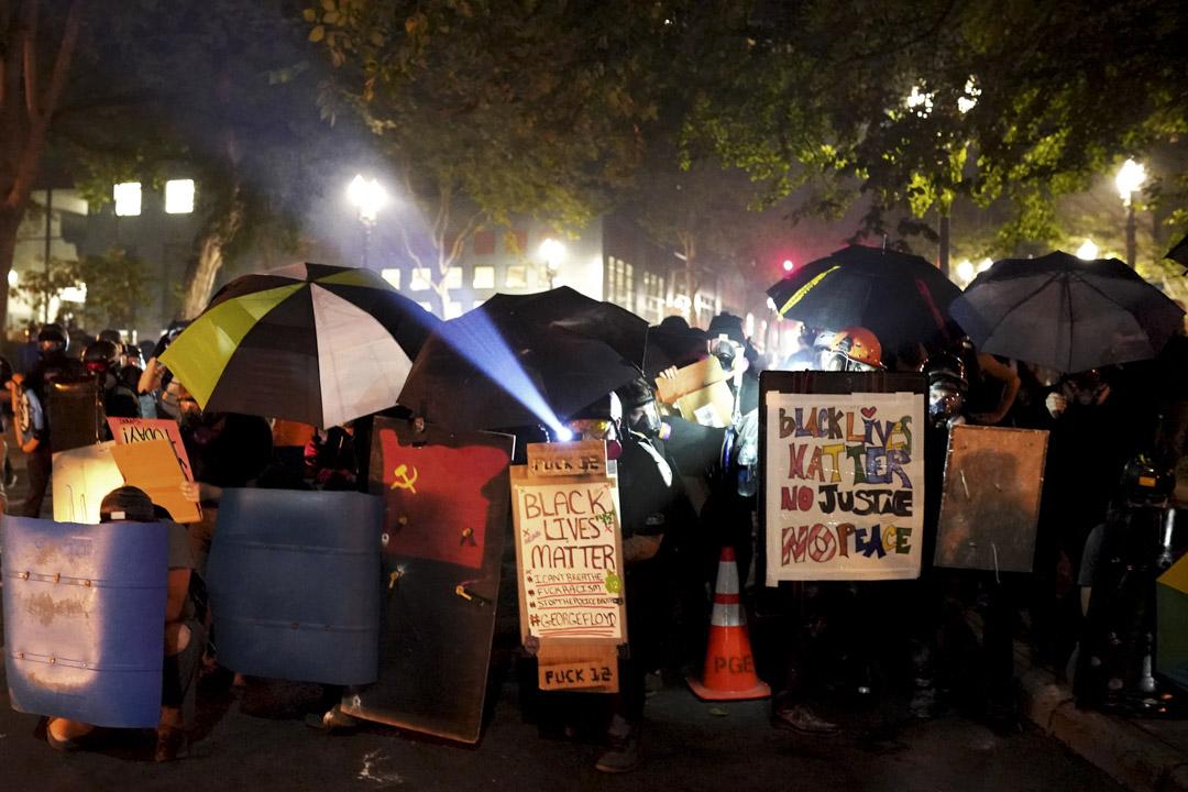 2020年7月21日,波特蘭示威者以傘及一些膠板築起防線,向警方推進。