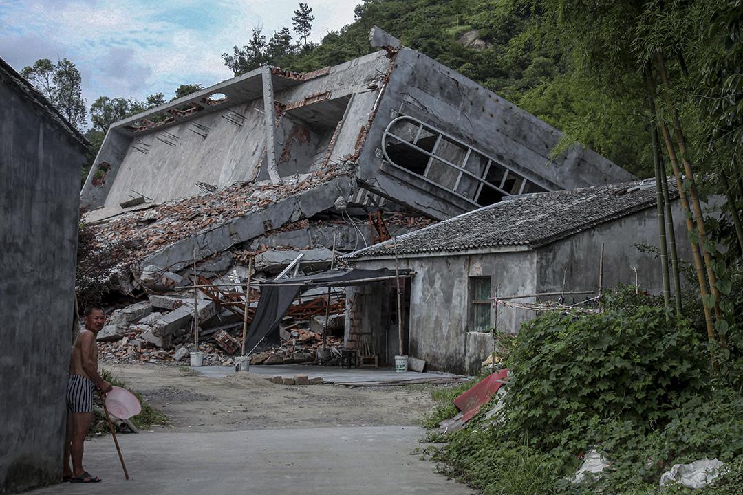 2014年7月16日中國浙江省溫州平陽縣,一名男子站在一個村莊遭拆毀天主教教堂附近。
