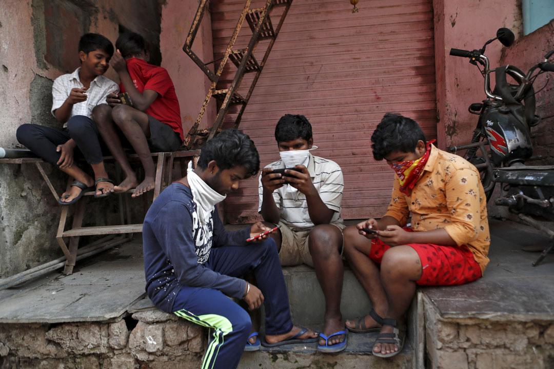 2020年4月9日,印度孟買,2019冠狀病毒病爆發期間,一群男孩看著他們的手機。