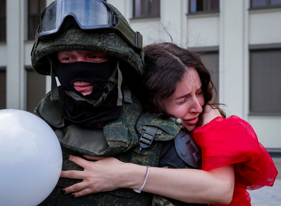 2020年8月14日,白羅斯首都明克斯,一名反政府示威參與者擁抱一名白羅斯內政部士兵。連日血腥鎮壓後,內政部士兵態度軟化,一支把守政府建築物的部隊應示威者要求,放下防暴盾牌。