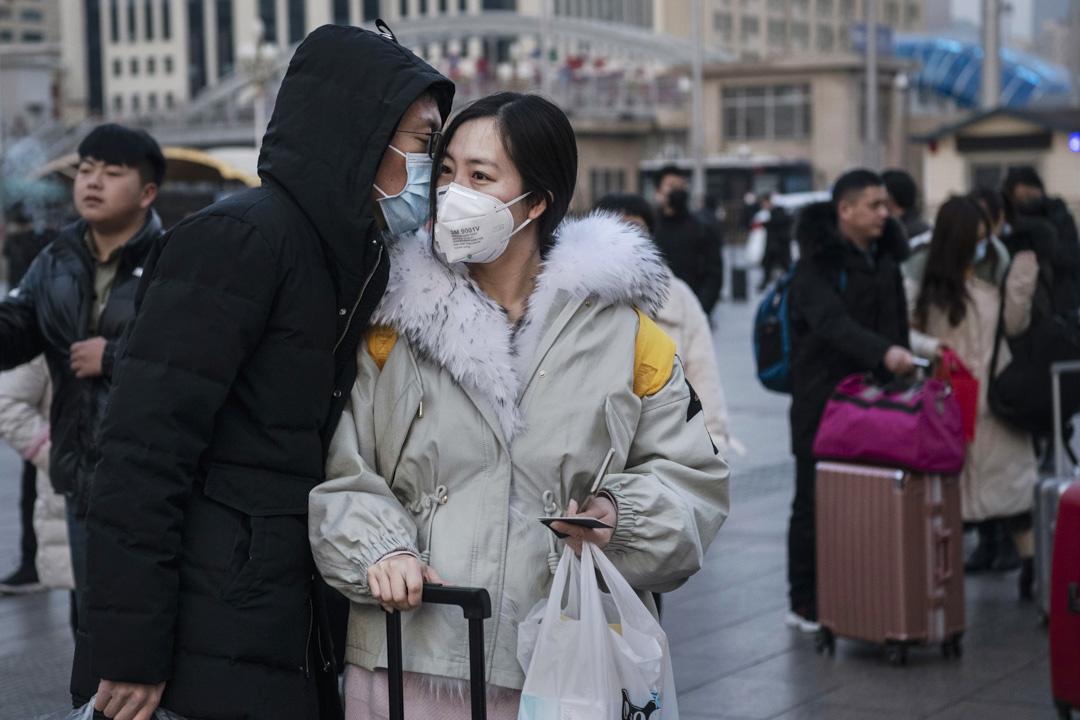 2020年1月21日,北京的春節前,一名男士在火車站親吻伴侶道別。 攝:Kevin Frayer/Getty Images