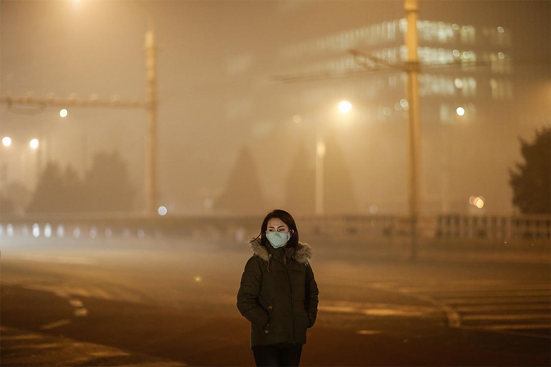 2015年11月30日北京,戴着口罩的婦女走在一個霧霾的晚上。