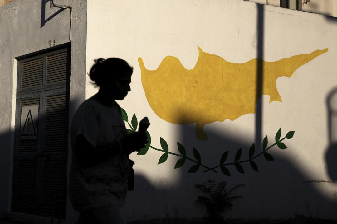 2017年7月7日,一名女士經過繪有塞浦路斯國旗圖案的一面牆。 攝:Yiannis Kourtoglou / Reuters