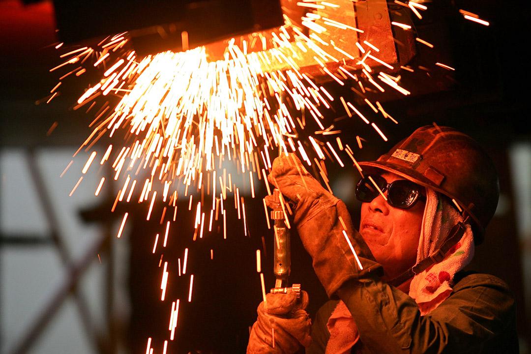 2010年8月16日,一名員工在台灣高雄的船廠焊接一艘船的部件。