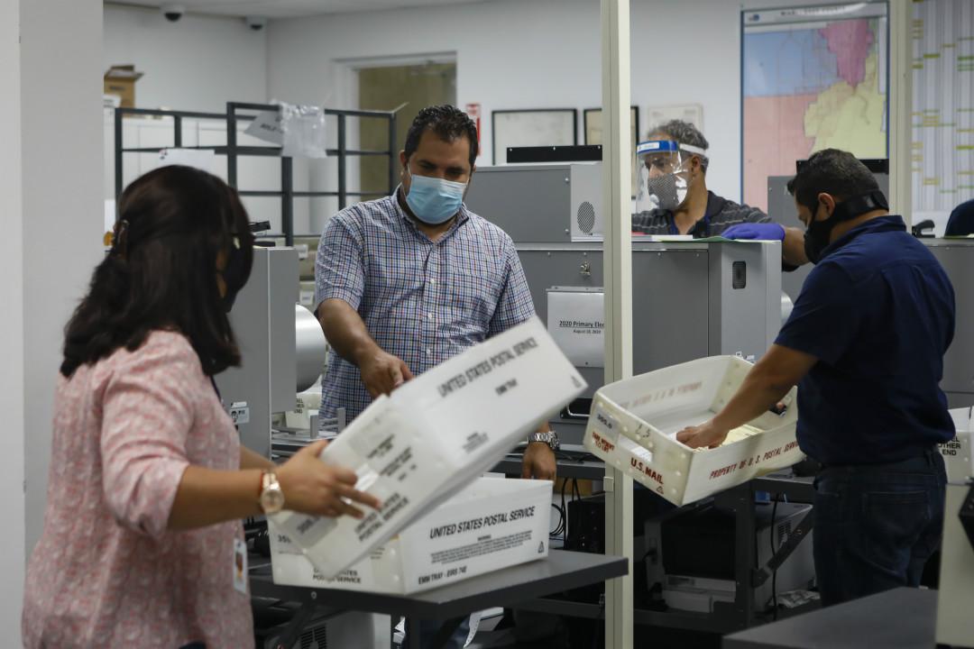 2020年8月18日,美國佛羅里達州邁阿密-戴德選舉部門,員工處理 USPS 盒子中待掃描的郵寄選票。 攝:Eva Marie Uzcategui/Getty Images