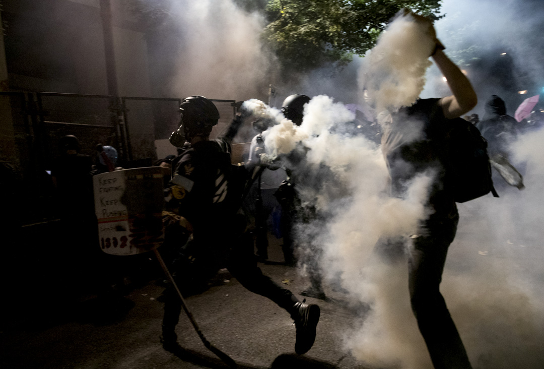 2020年7月29日,波特蘭一場遊行中,示威者將催淚彈罐拾起向對方扔回。