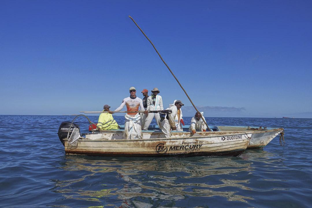 漁民在「若潮號」擱淺的附近海域清理油污。