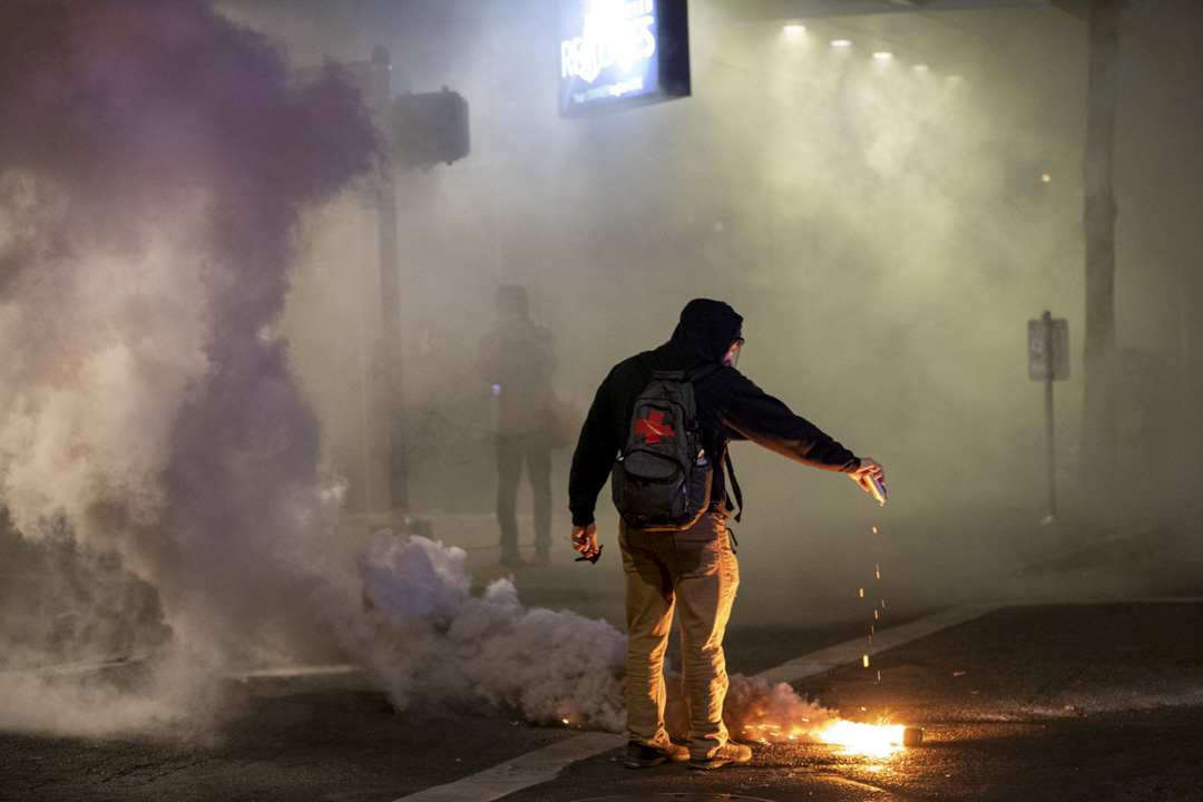 2020年7月29日,波特蘭一場抗議中,一名醫療志願隊人員在催淚彈上倒水。