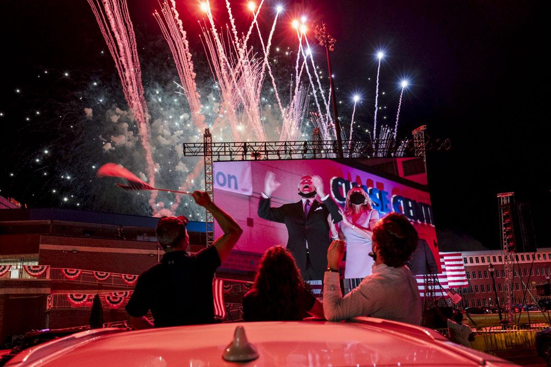 2020年8月20日,美國特拉華州,民主黨全國代表大會第四天,民主黨總統候選人拜登和妻子出現在巨大的戶外屏幕上,煙花在夜空發放。 攝:Carolyn Kaster/AP/達志影像