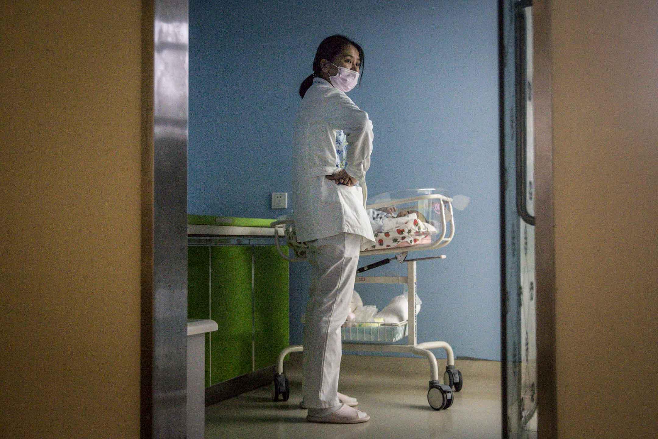 2020年3月12日,武漢一家私立婦產醫院,一名產婦護士在照顧新生兒時戴著口罩。