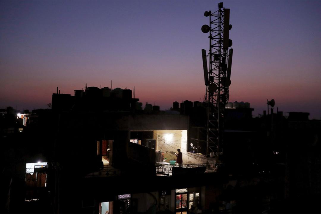 2020年4月26日印度新德里,2019冠狀病毒爆發期間一個人留在家中站在陽台使用手機。