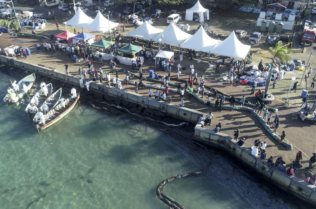 義工在「若潮號」擱淺的岸邊準備臨時浮標,阻止油污擴散。