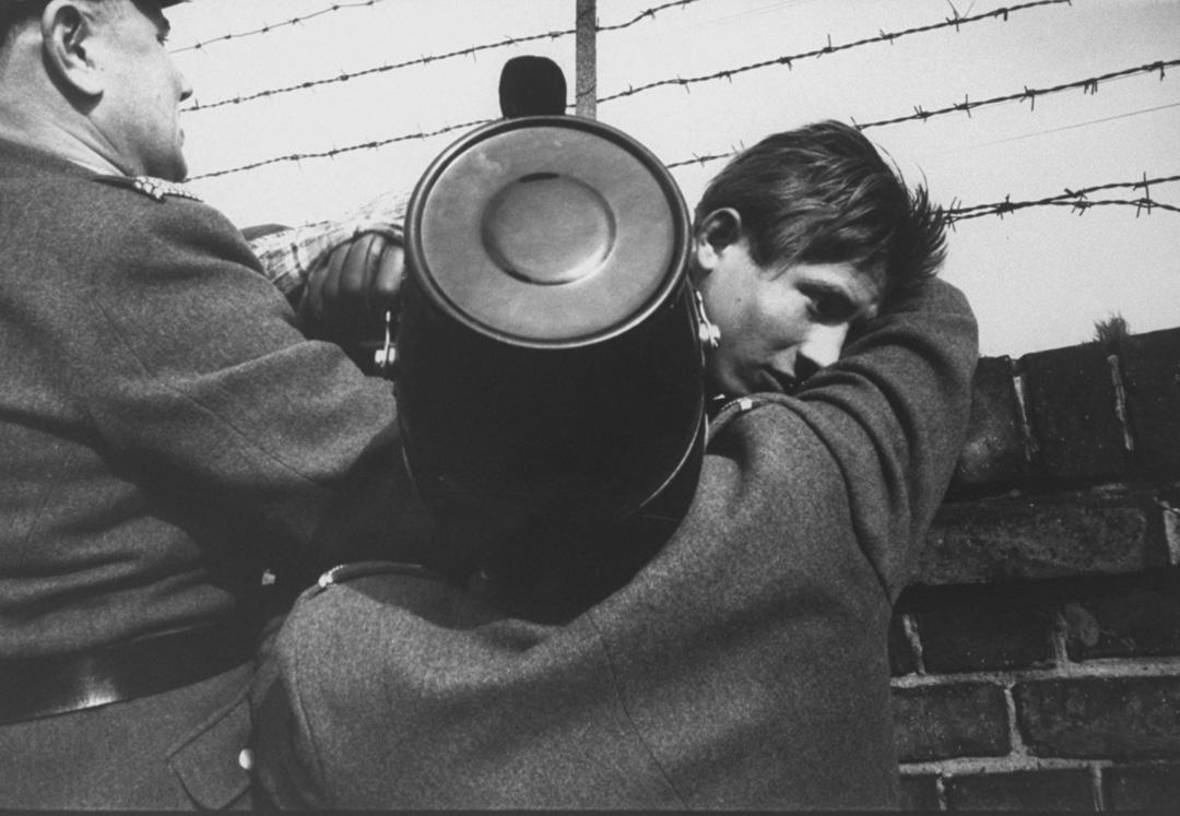 兩名西柏林警察幫助17歲的男孩從東柏林攀牆而來。