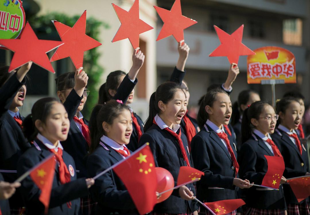 2019年2月28日,中國內蒙古自治區呼和浩特市,學生們在表演名為「我和我的祖國」的歌曲時舉著中國國旗。