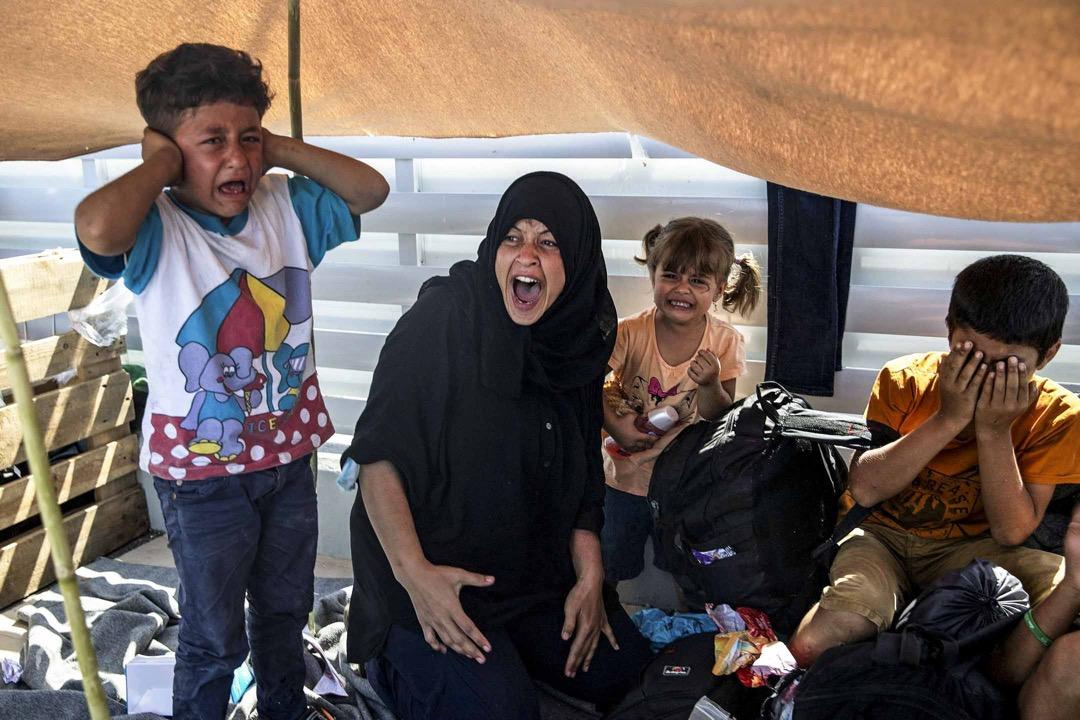 2020年9月12日,希臘萊斯沃斯島,逃離莫里亞難民營火災的難民與當地警方對峙,一名女子與孩子們在旁痛哭。