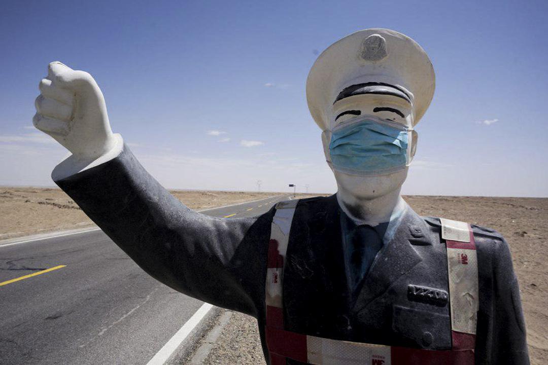 烏魯木齊的公路上有一個被戴上口罩的交通指揮員雕塑。