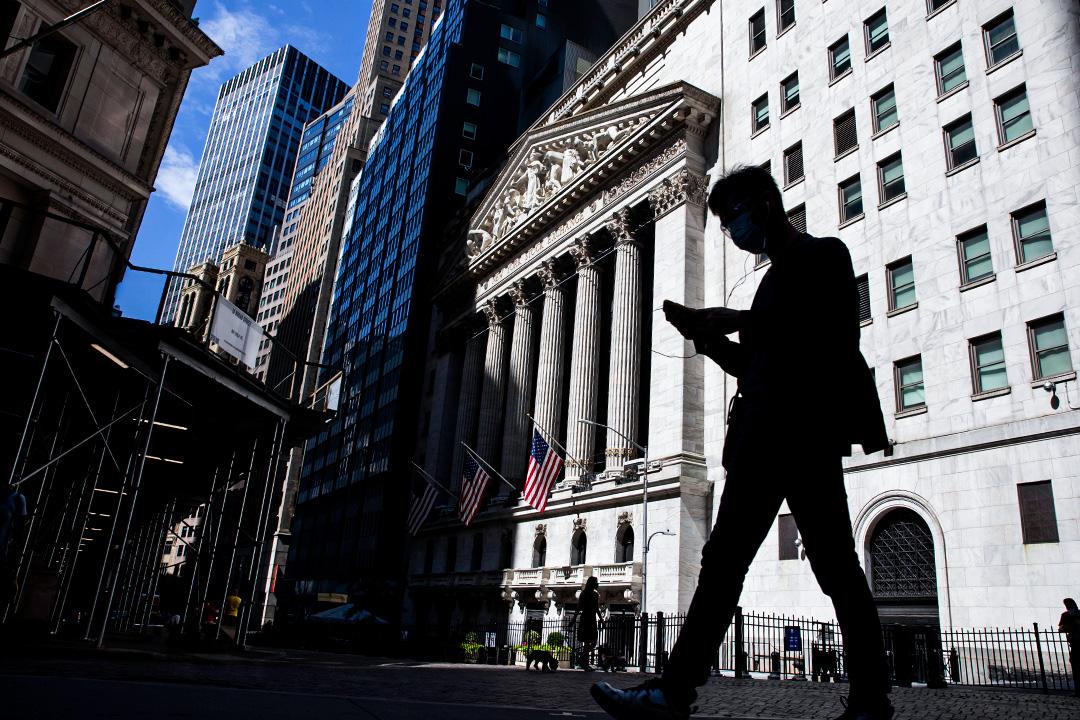 2020年7月20日,一名戴著口罩的行人在美國紐約證券交易所(NYSE)前經過時看著智能手機。