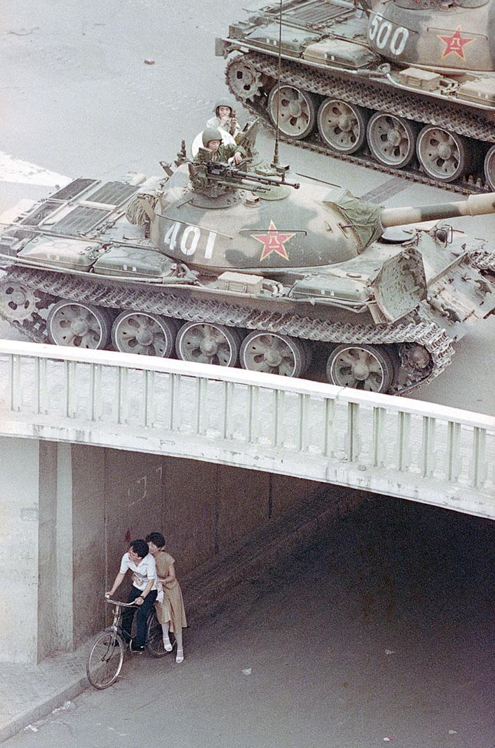 1989年6月5日,一對中國情侶騎著單車以地下通道作掩護,坦克在橋上行走。