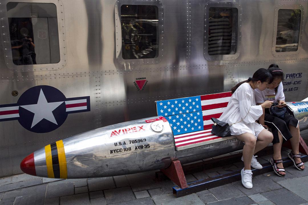 2018年7月6日,中國婦女看著手機坐在美國國旗的火箭形長凳上。
