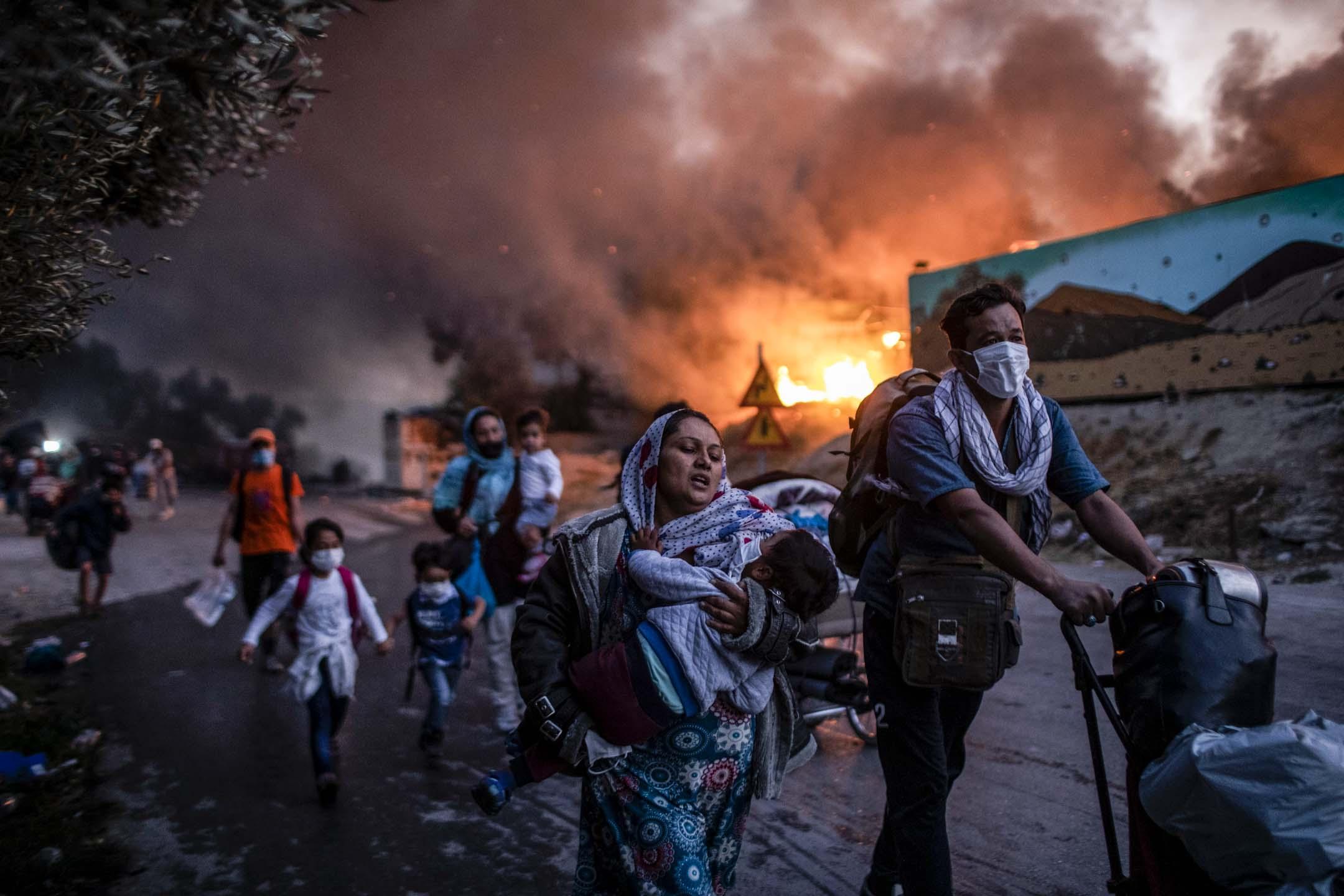 2020年9月9日,希臘萊斯沃斯島、莫里亞難民營發生火災,難民營居民趕忙逃離現場。 攝:Petros Giannakouris/AP/達志影像