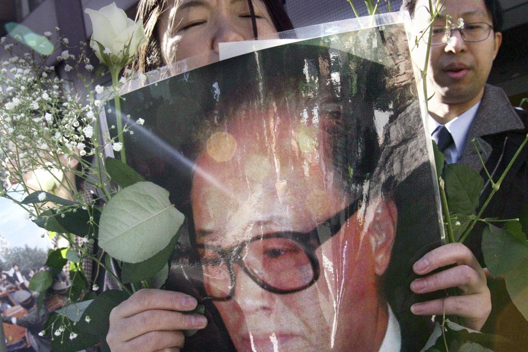 2005年1月21日,一名居住在日本的民主人士,在東京中國大使館前的一次集會上手持已故前中共中央總書記趙紫陽的肖像悼念。