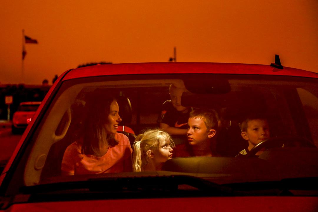 2020年9月9日,加州一個家庭的公路旅行中,母親與孩子們坐在汽車內,車外被一片橙色的天空籠罩著。 攝:Gabrielle Lurie/The San Francisco Chronicle via Getty Images