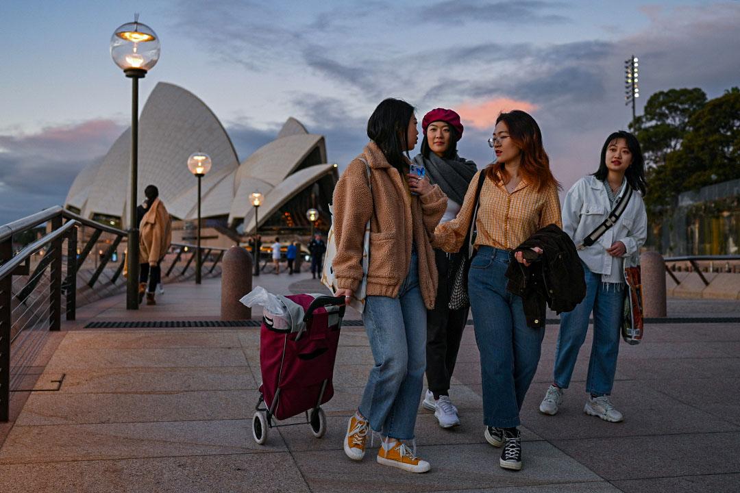 2020年6月24日悉尼,2019冠狀病毒病爆發期間,來自中國的國際學生在悉尼歌劇院旁沿著海濱散步。