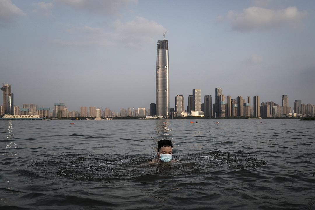 2020年6月30日在中國武漢,一個戴著口罩的男孩在被洪水淹沒的公園裡游泳。