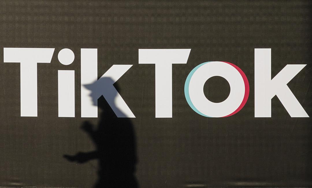 2020年9月21日,一名拿著智能手機的年輕人在TikTok廣告前走過。 攝:Sean Gallup/Getty Images