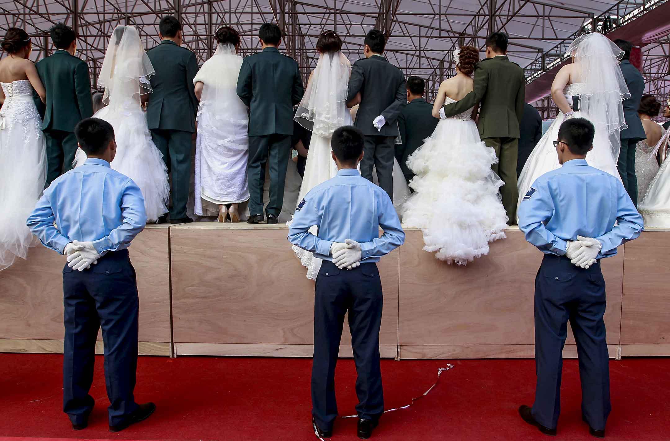 2013年10月18日,台北舉行的一個集體婚禮上,士兵們在台下,以防新婚夫婦合影時不小心摔倒。 攝:Pichi Chuang/Reuters/達志影像