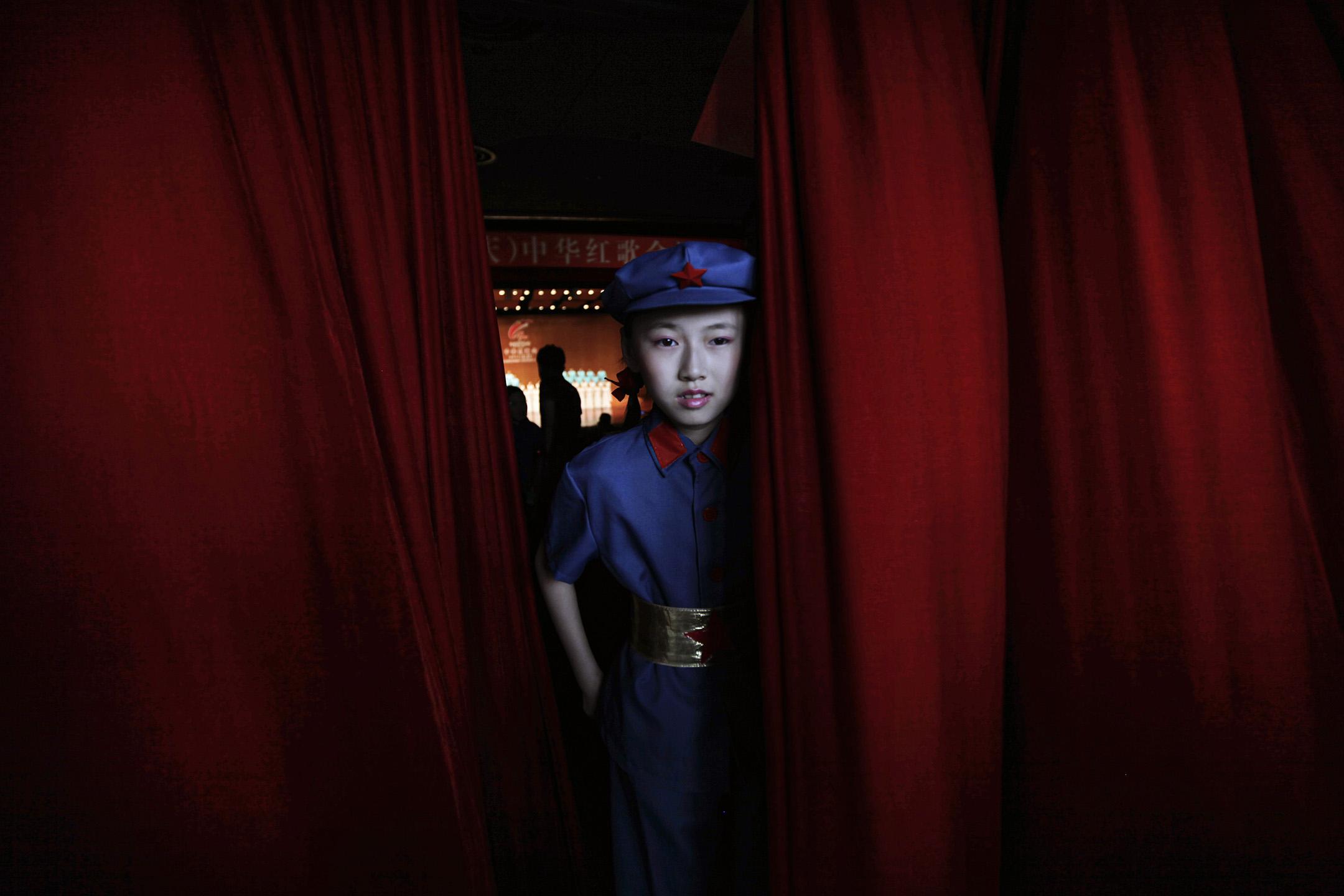 2011年6月30日重慶歌劇院,慶祝中國共產黨成立90週年,一場革命歌唱比賽中,一名身著中國紅軍士兵的女學生躲在紅色的帷幕後。 攝:Jason Lee/Reuters/達志影像