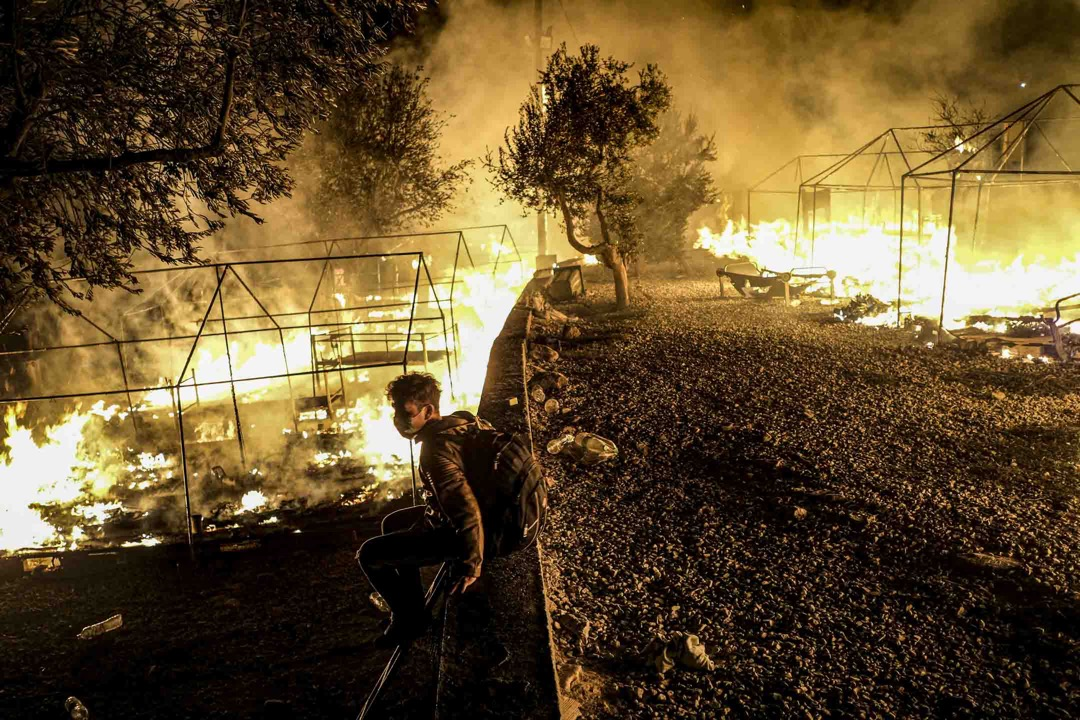 2020年9月9日,希臘萊斯沃斯島、莫里亞難民營發生火災,一名逃到希臘尋求庇護者坐看著營地被燒毀。