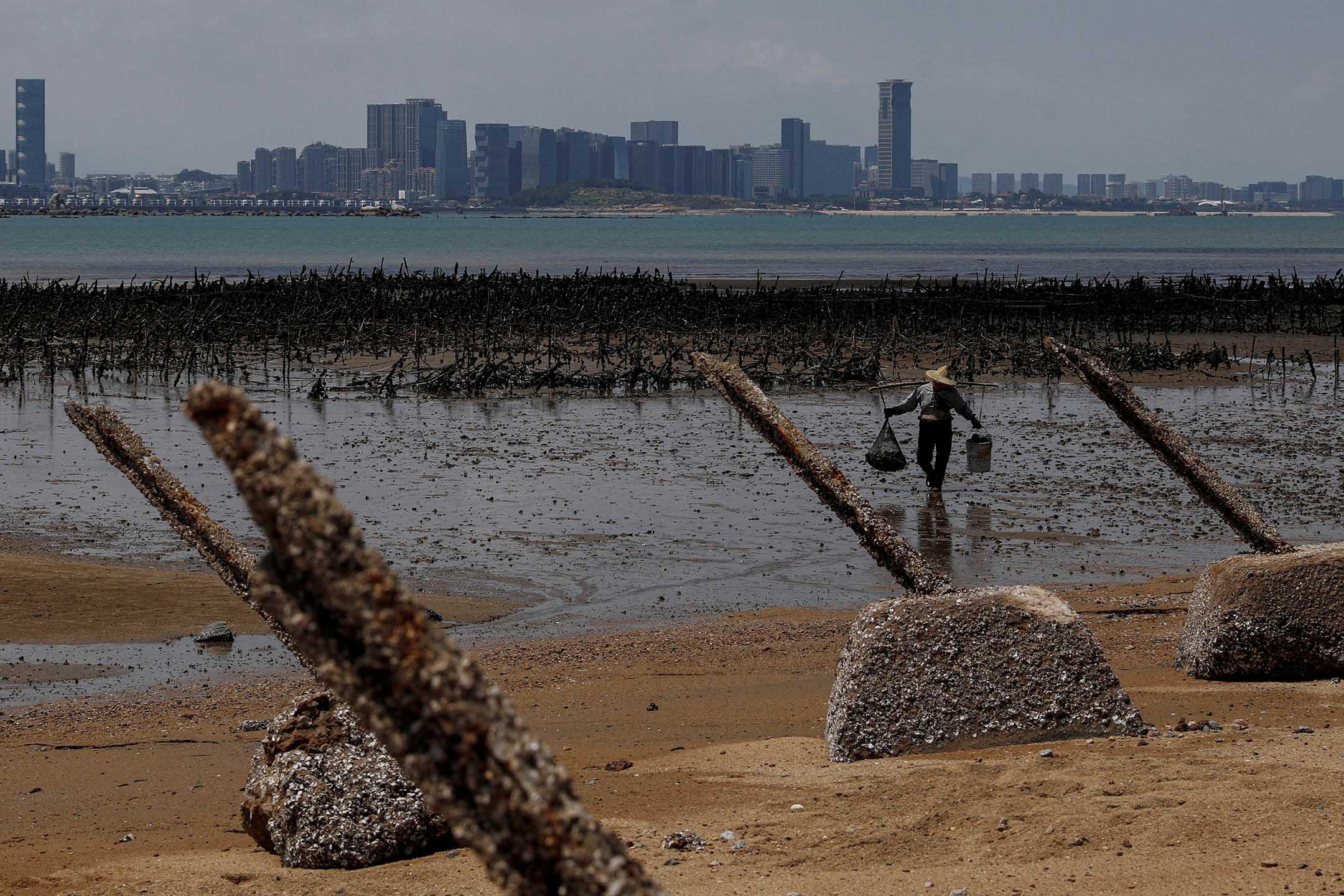 2018年8月20日台灣小金門,823砲戰60週年之際,一位牡蠣養殖者在海邊行走。 攝:Tyrone Siu/Reuters/達志影像
