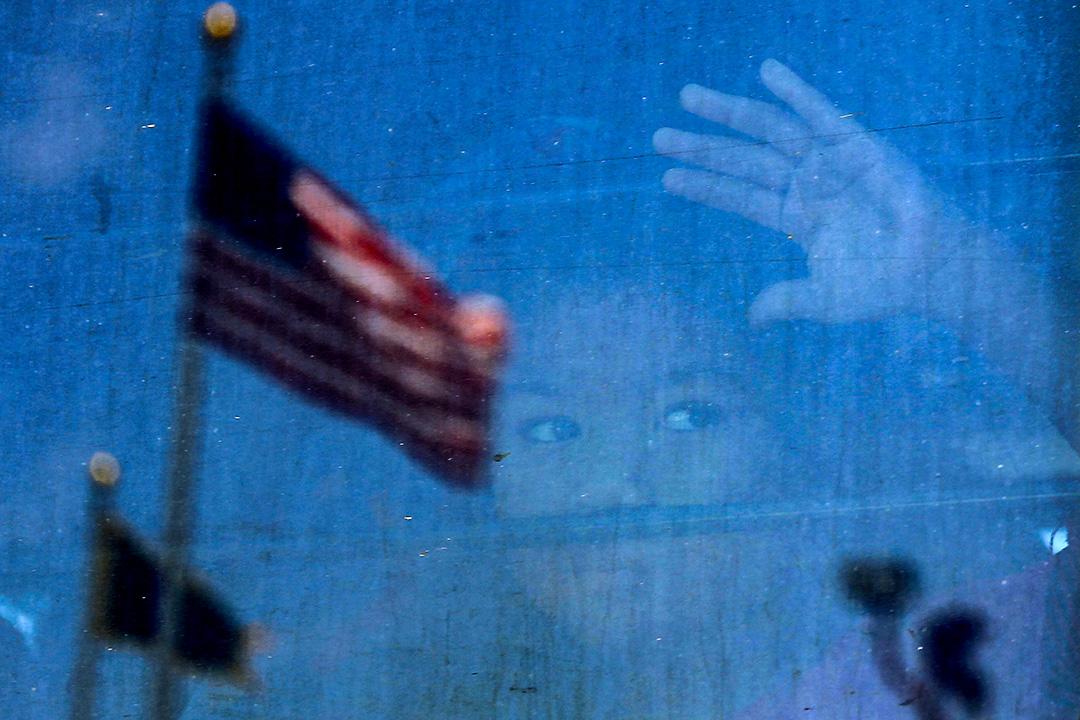 2018年6月23日德克薩斯州麥卡倫,抗議者包圍公共汽車,試圖阻止美國海關和邊境保護拘留中心以公共汽車運送移民兒童,一名移民兒童看著公共汽車的窗戶。
