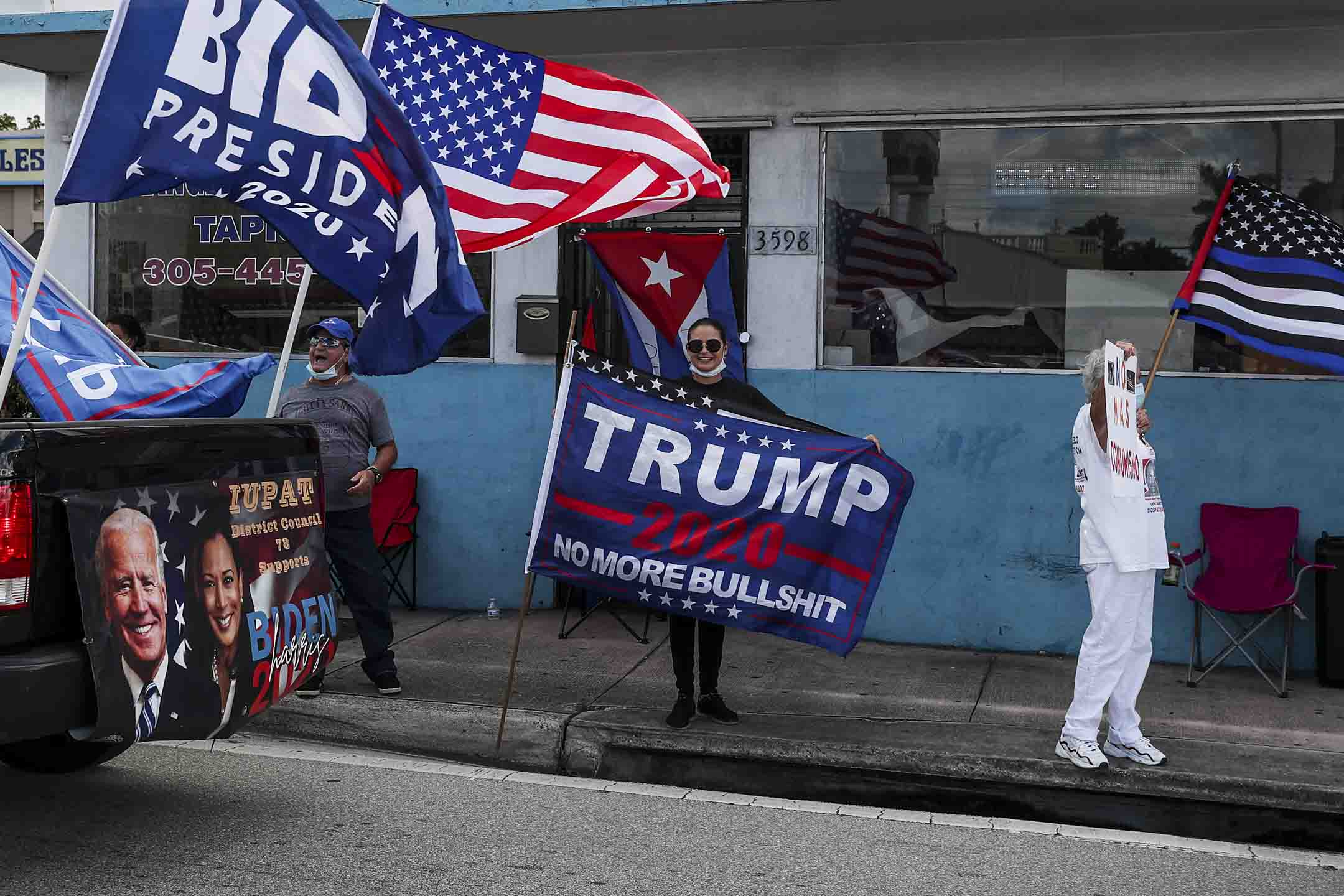 2020年10月18日,佛羅里達州邁阿密舉行的工人大篷車活動期間,在車上的拜登支持者經過在路上的特朗普支持者。 攝: Joe Raedle/Getty Images