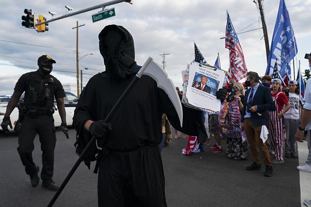2020年10月5日美國馬里蘭州貝塞斯達的國家軍事醫學中心外,反對美國總統特朗普的示威者打扮成死神走過支持者的集會。