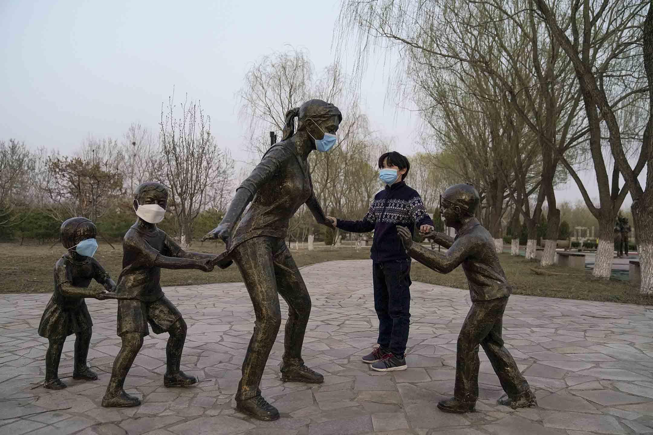 2020年3月22日,北京一個孩子在公園裡觸摸一組戴著口罩的雕像。