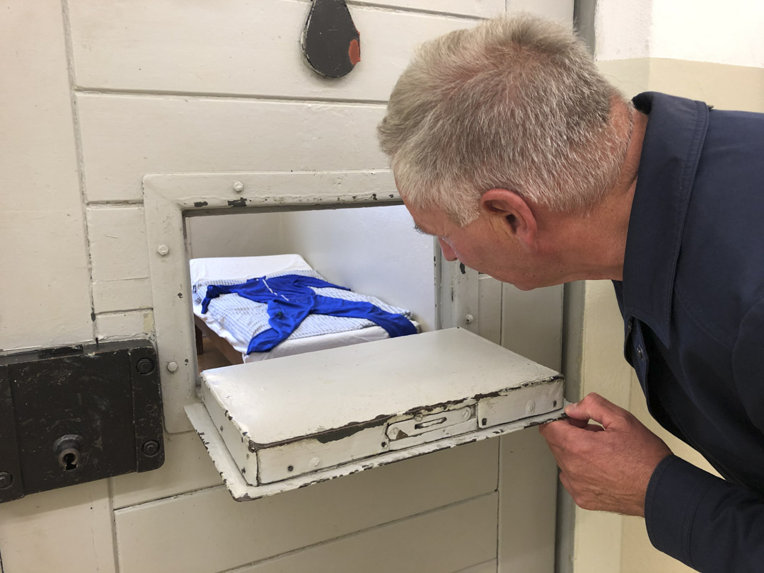 舒爾茨透過一扇監查窗,向訪客介紹霍恩施豪森監獄內的一間牢房。