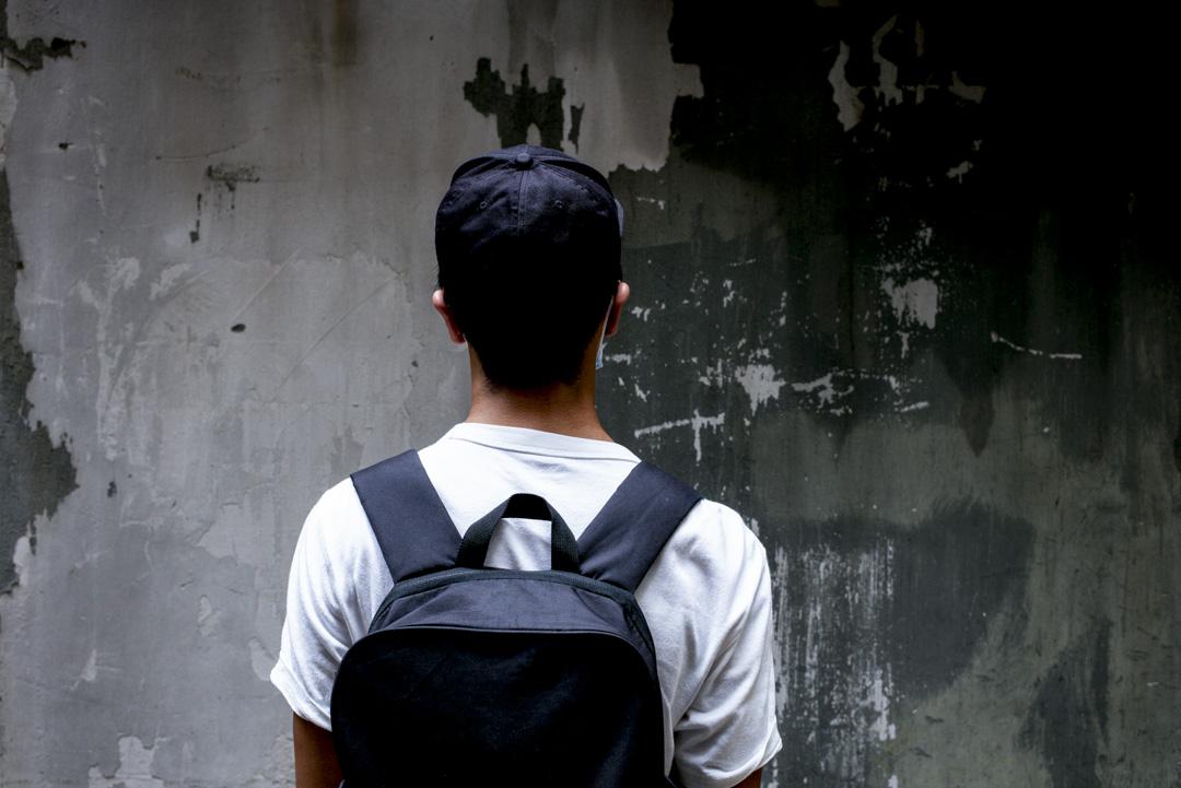 李俊文在九龍的一條後巷面向牆壁。