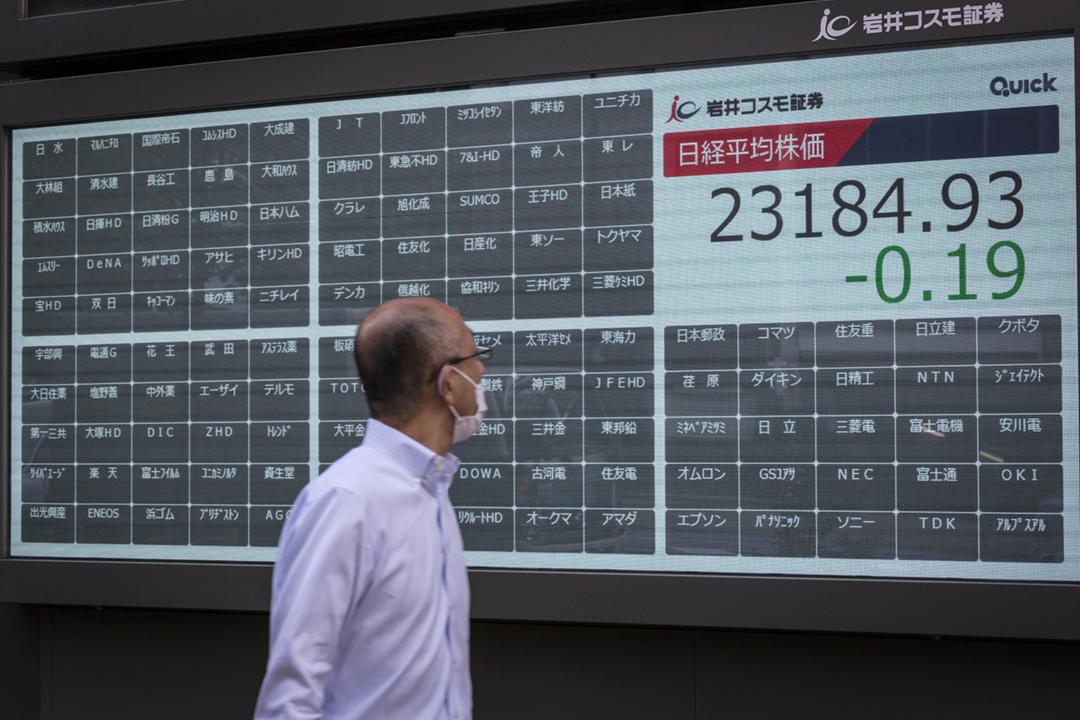 2020年10月1日,東京證券交易所的系統硬件設備發生故障而全日停市,一名途人經過沒有任何交易資訊更新的螢幕。 攝:Yuichi Yamazaki / Getty Images