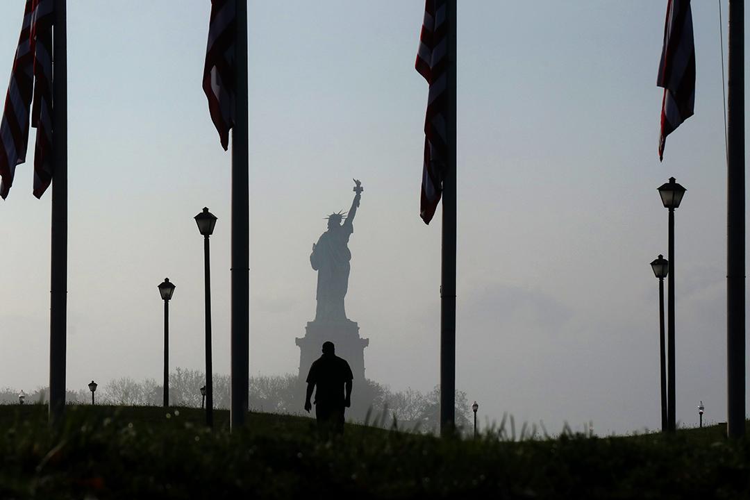 2020年6月6日紐約,一個人走在晨霧中在自由女神像前。