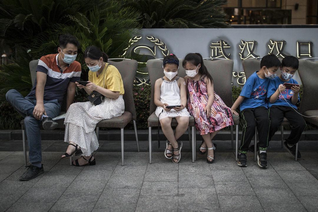2020年5月28日,武漢喜來登酒店外,家長與兒童在等待時同樣使用手機消磨時間。
