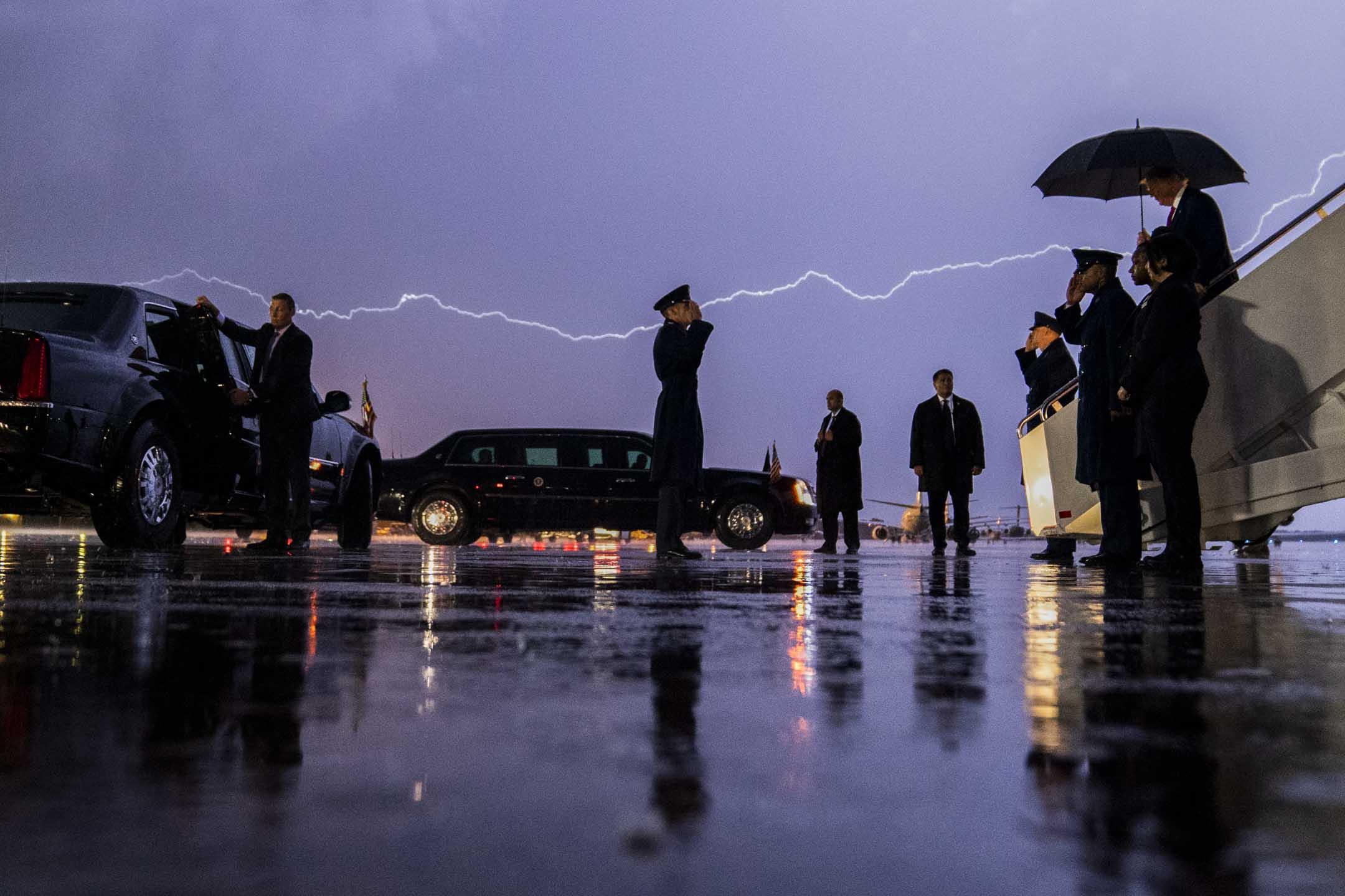 2020年8月28日,美國總統特朗普參加一場競選集會後乘空軍一號抵達機場,撐著一把傘沿著樓梯走下,天空有一道閃電劃過。 攝:Evan Vucci//AP/達志影像