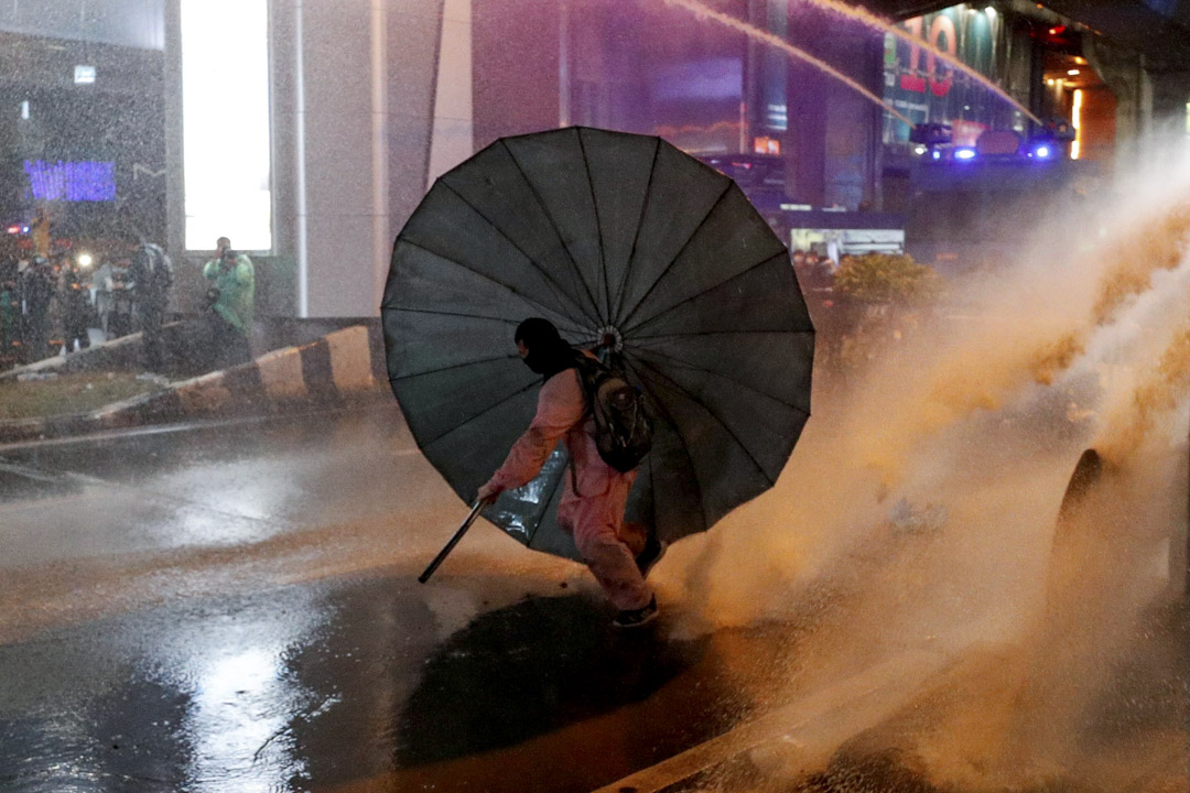 2020年10月16日泰國曼谷,一場反政府抗議活動中一名男子躲在傘下。