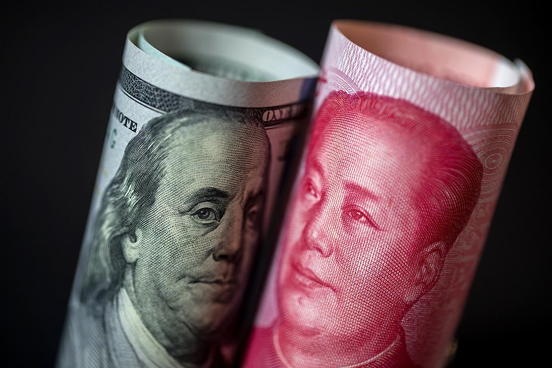 2019年4月15日,一張一百美元的鈔票和人民幣一百元鈔票。 攝:Paul Yeung/Bloomberg via Getty Images