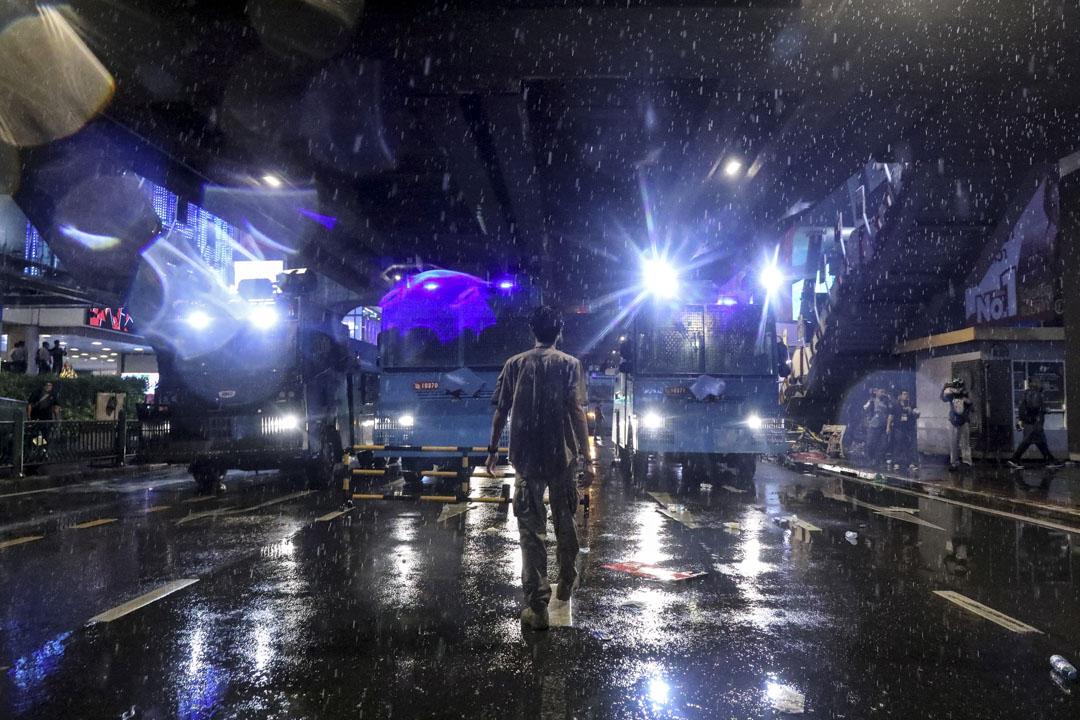 2020年10月16日泰國曼谷,一場反政府抗議活動中,一名男子走在馬路中水砲車的前方。