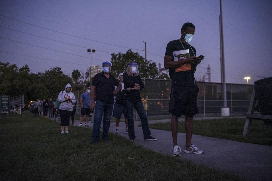 2020年10月13日,美國德克薩斯州休斯頓舉行的投票站外,戴著口罩的選民排隊提前投票。