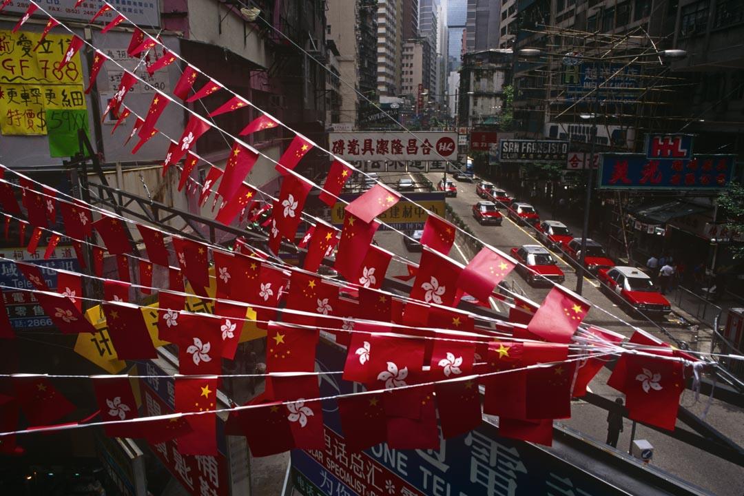 1997年6月30日,香港回歸前一天,街上有特區區旗與國旗飄揚。